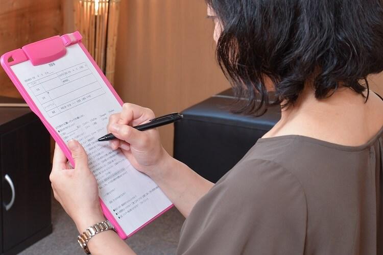 待合で質問票を記入する女性